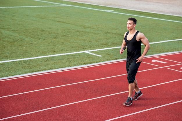 Junger männlicher athlet der eignung, der auf rennstrecke läuft Kostenlose Fotos