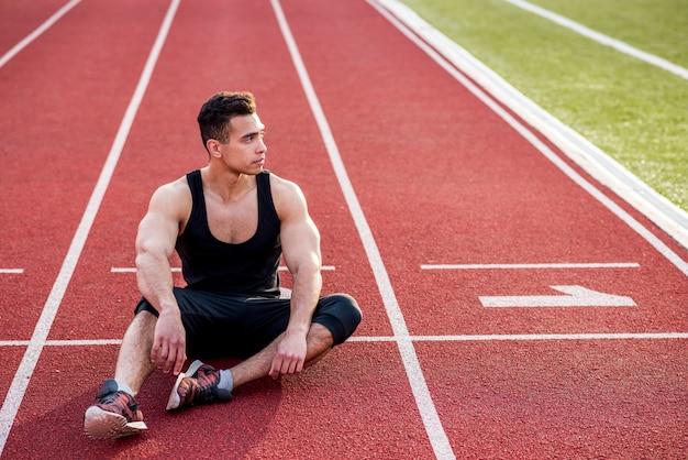 Junger männlicher athlet der eignung, der auf roter rennstrecke im stadion sich entspannt Kostenlose Fotos
