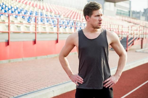 Junger männlicher athlet der eignung mit seinen händen auf der hüfte, die vor arena steht Kostenlose Fotos
