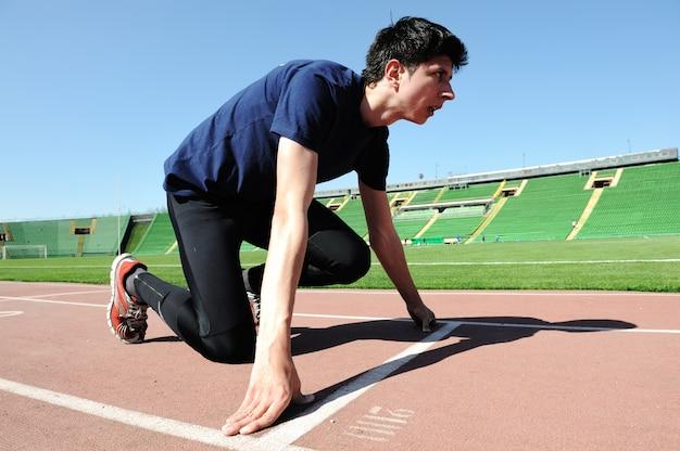Junger männlicher athlet ist am anfang des laufbandes am stadion Premium Fotos