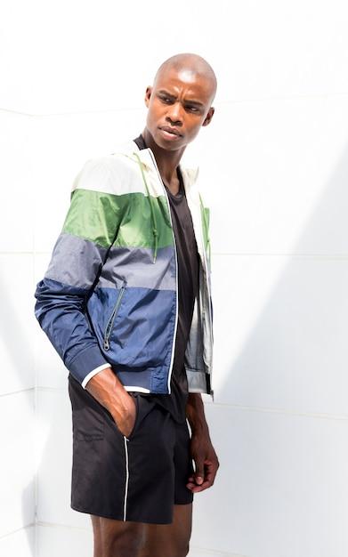 Junger männlicher athlet mit den händen in seiner tasche, die gegen weiße wand steht Kostenlose Fotos