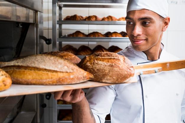 Junger männlicher bäcker, der mit der hölzernen schaufel frisch gebackenes brot vom ofen herausnimmt Kostenlose Fotos