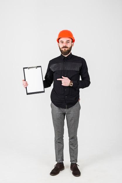 Junger männlicher bauingenieur, der das klemmbrettgestikulieren hält Kostenlose Fotos