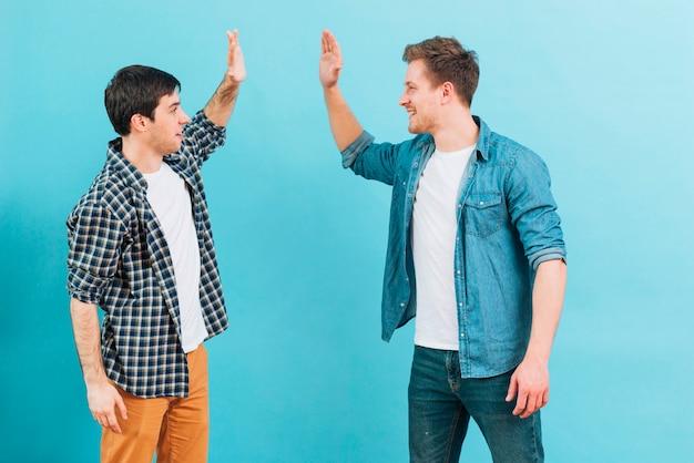 Junger männlicher freund, der hoch fünf gegen blauen hintergrund gibt Kostenlose Fotos