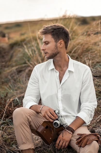 Junger männlicher hippie in einem weißen hemd mit alter kamera in seinen händen, die in der natur aufwerfen. erkunde unbekannt und sieh cool aus in einer seltsamen szenerie. Premium Fotos