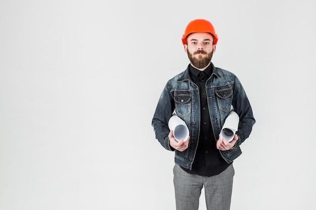 Junger männlicher ingenieur, der pläne in seiner hand hält Kostenlose Fotos