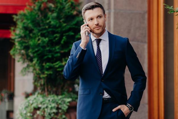 Junger männlicher mann hat telefongespräch, schaut sicher in die ferne Premium Fotos