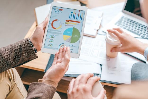 Junger männlicher ökonom mit touchpad, der auf finanzdiagramm auf bildschirm zeigt, während daten dem kollegen erklärt Premium Fotos