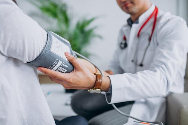 Junger männlicher psysician mit messendem blutdruck des patienten Kostenlose Fotos