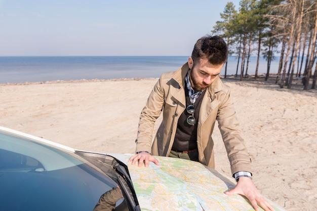 Junger männlicher reisender, der nach dem standort auf karte über der automütze am strand sucht Kostenlose Fotos