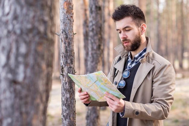 Junger männlicher reisender, der nach dem standort in der karte sucht Kostenlose Fotos