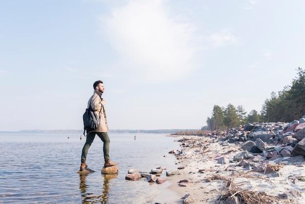 Junger männlicher reisender mit ist der rucksack, der ansicht betrachtet Kostenlose Fotos