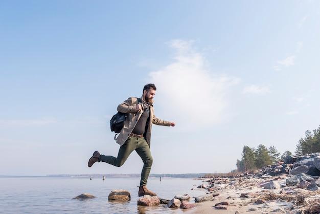 Junger männlicher reisender mit seinem rucksack, der über die steine auf see läuft Kostenlose Fotos