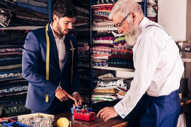 Junger männlicher schneider, der seinem kunden bunte spule im shop zeigt Kostenlose Fotos