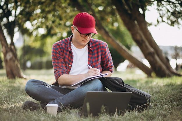 Junger männlicher student, der an einem computer im park arbeitet Kostenlose Fotos