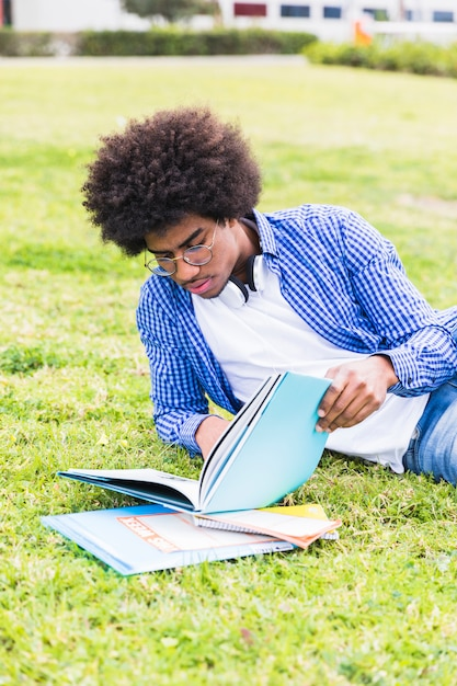 Junger männlicher student, der auf dem rasen das buch lesend sich lehnt Kostenlose Fotos