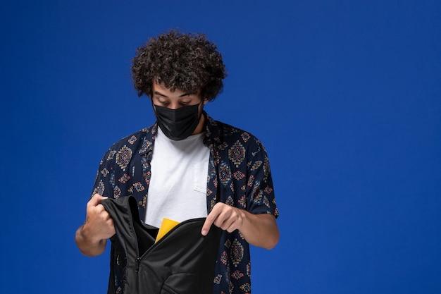 Junger männlicher student der vorderansicht, der schwarze maske trägt und rucksack auf hellblauem hintergrund hält. Kostenlose Fotos