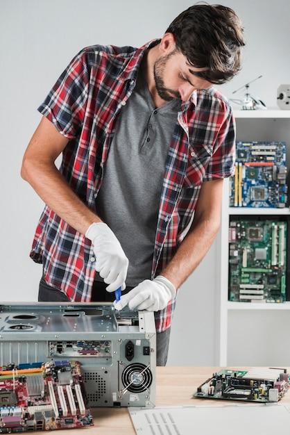 Junger männlicher techniker, der an computer-cpu in der werkstatt arbeitet Kostenlose Fotos