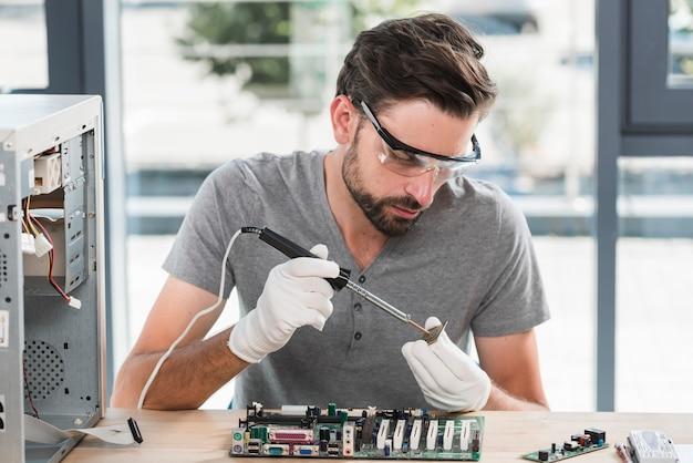 Junger männlicher techniker, der an computer ram arbeitet Kostenlose Fotos