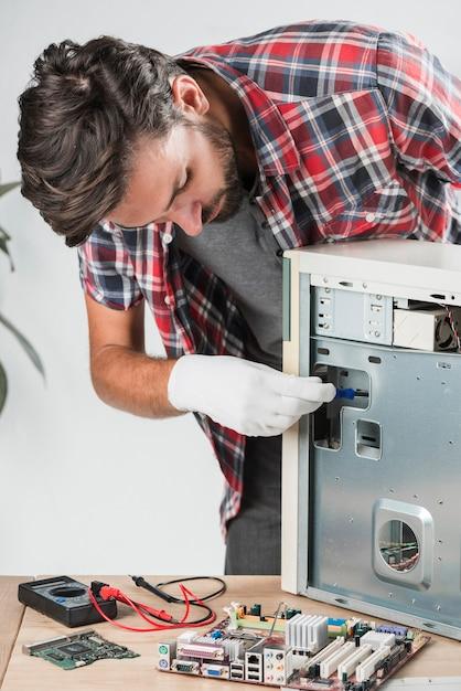 Junger männlicher technikeruntersuchungscomputer in der werkstatt Kostenlose Fotos