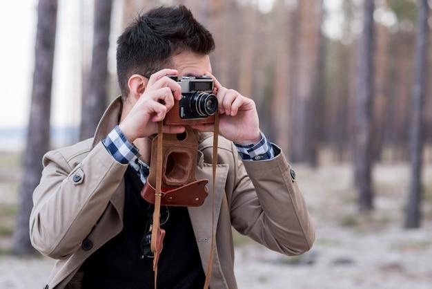 Junger männlicher wanderer, der fotos mit kamera macht Kostenlose Fotos