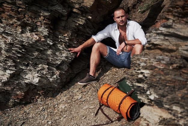 Junger männlicher wanderer mit rucksack, der auf einem felsigen massiv während des ruhigen sommersonnenuntergangs entspannt. travel lifestyle abenteuer urlaub konzept Kostenlose Fotos