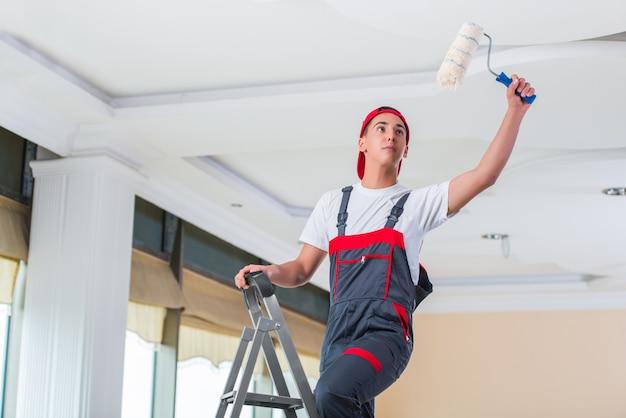 Junger maler, der die decke im baukonzept malt Premium Fotos