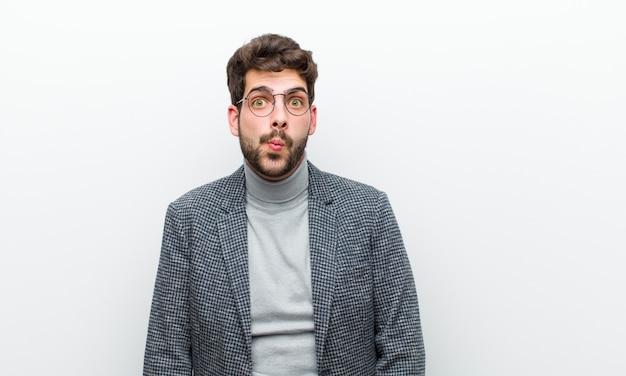 Junger managermann, der lippen zusammen mit einem netten, spaß, glücklichen, reizenden ausdruck, einen kuss gegen weiße wand sendend bedrängt Premium Fotos