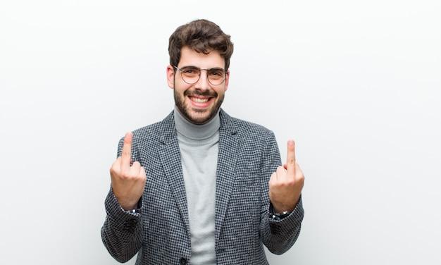 Junger managermann, der provokativ, aggressiv und obszön sich fühlt und den mittelfinger, mit einer rebellischen haltung gegen weiß leicht schlägt Premium Fotos