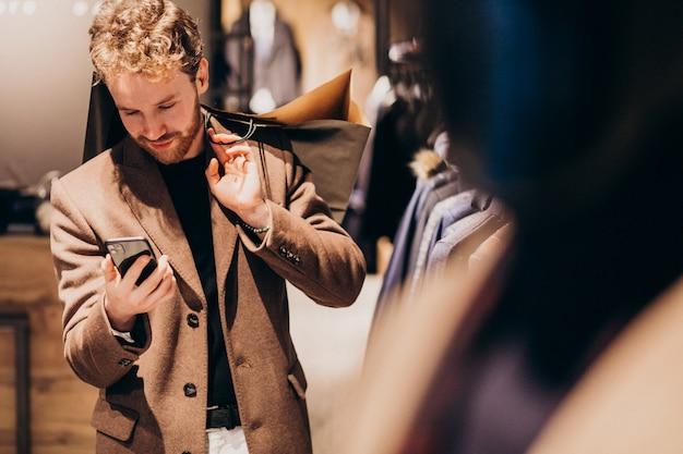 Junger mann am herrenbekleidungsshop sprechend am telefon Kostenlose Fotos
