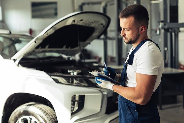 Junger mann am service, der auto repariert Kostenlose Fotos