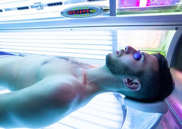 Junger mann am solarium im schönheitssalon. Premium Fotos