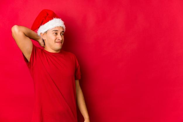 Junger mann am weihnachtstag, der zurück vom kopf berührt, eine wahl denkt und trifft. Premium Fotos
