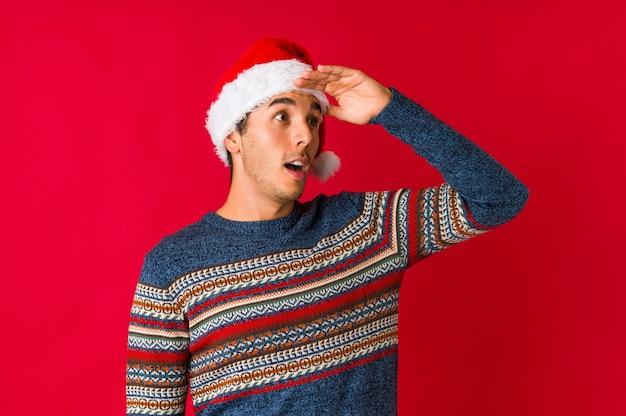 Junger mann am weihnachtstag zuckt mit den schultern und die offenen augen, die verwirrt werden. Premium Fotos