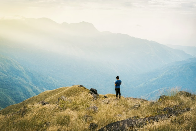 Junger mann asien-tourist des instagram-filters am berg passt über den nebelhaften und nebeligen morgensonnenaufgang auf Premium Fotos