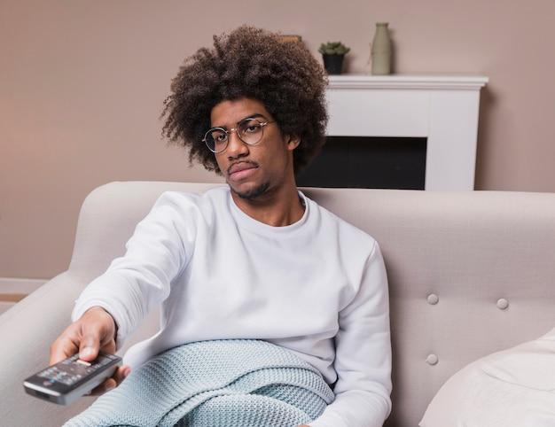 Junger mann auf der couch mit fernbedienung Kostenlose Fotos