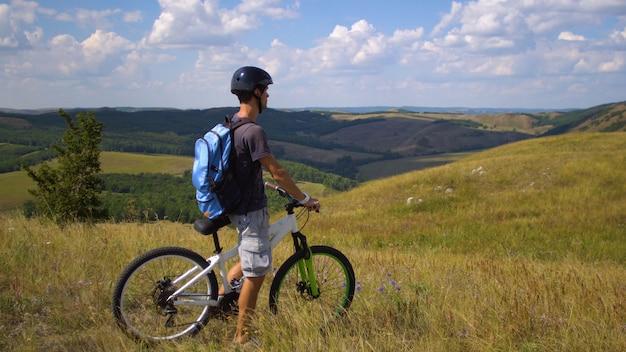 Junger mann auf einem fahrrad unter dem grünen hügel gegen einen himmel mit wolken Premium Fotos