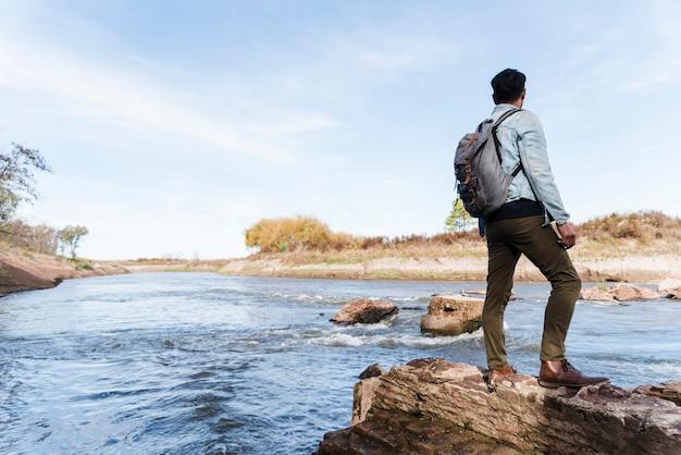 Junger mann auf felsen nahe dem see Kostenlose Fotos