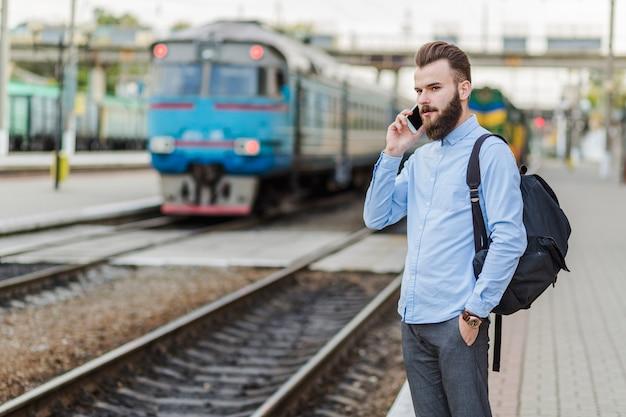 Junger mann, der am bahnhof unter verwendung des mobiltelefons steht Kostenlose Fotos
