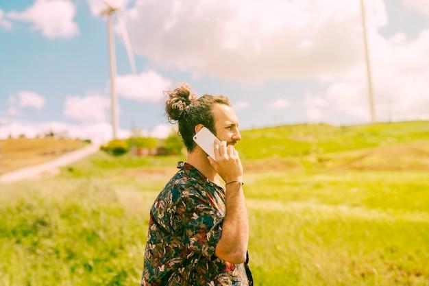 Junger mann, der am handy in ländlichem sich unterhält Kostenlose Fotos