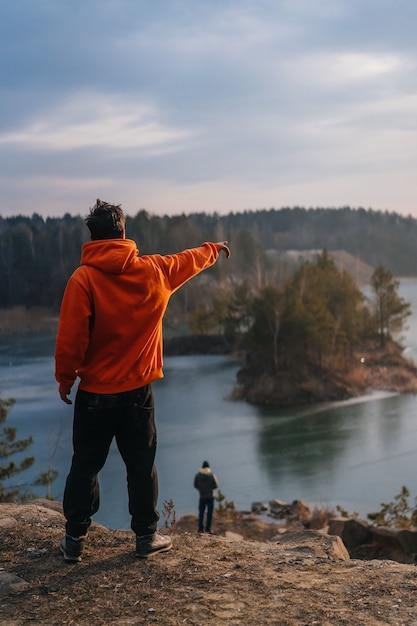 Junger mann, der am rand einer klippe und des zeigens steht Kostenlose Fotos