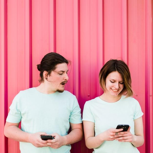 Junger mann, der am smartphone ihrer freundin verwendet handy ausspioniert und späht Kostenlose Fotos
