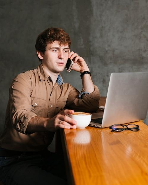 Junger mann, der am telefon im büro spricht Kostenlose Fotos