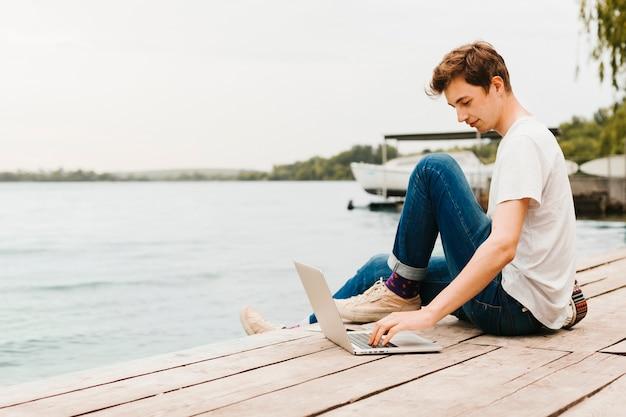 Junger mann, der an dem laptop durch den see arbeitet Kostenlose Fotos