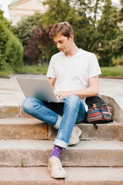 Junger mann, der an dem laptop im park arbeitet Kostenlose Fotos
