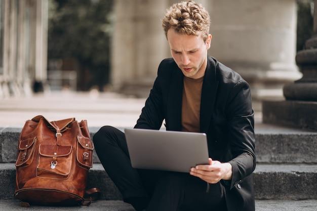 Junger mann, der an einem computer durch die universität arbeitet Kostenlose Fotos