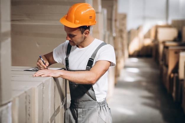 Junger mann, der an einem lager mit kästen arbeitet Kostenlose Fotos