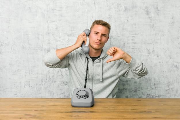 Junger mann, der an einem weinlesetelefon unten zeigt daumen spricht und abneigung ausdrückt. Premium Fotos