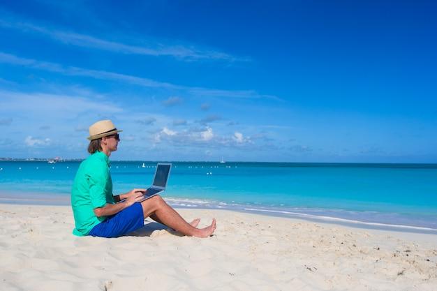 Junger mann, der an laptop am tropischen strand arbeitet Premium Fotos