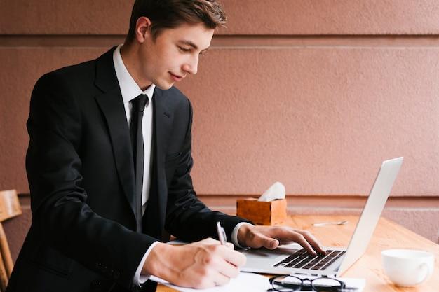 Junger mann, der an laptop im büro arbeitet Kostenlose Fotos